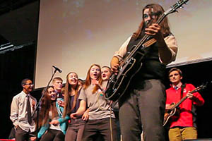 Musician Seth Bernard playing guitar on stage with high school students watching
