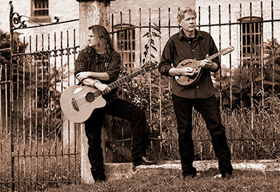 guitar player and mandolin player in from of gothic fence