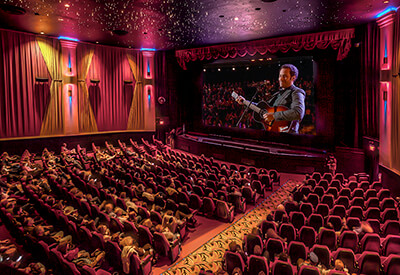 wide interior shot of movie theater with guitar player on screen
