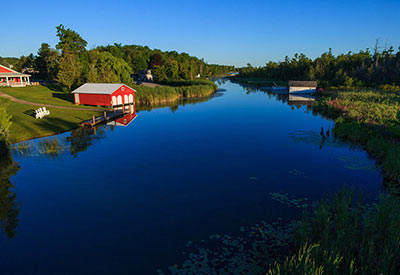 calm river on summer day with red boat house