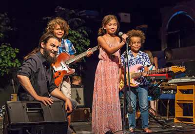 male music teacher on stage with three children with instruments