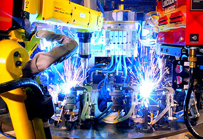 two industrial robots welding and sparks flying