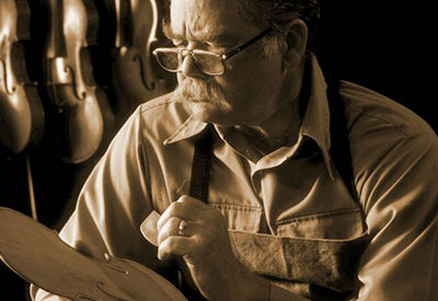 older violin maker workinig on instrument
